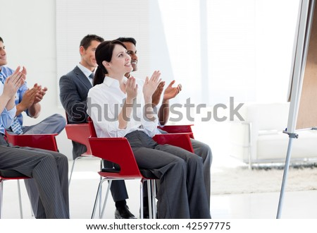 Multi-ethnic business people clapping at the end of a conference in the office