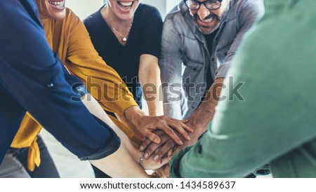 Multi-ethnic business people putting their hands on top of each other. Business team making a stack of hands showing unity. Stock photo ©