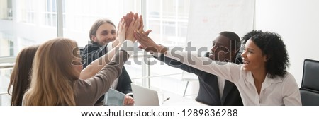 Multi-ethnic business people sitting at desk boardroom celebrating success giving high five feels happy excited, team spirit unity concept. Horizontal panoramic photo banner for website header design