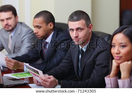 Multi ethnic business team at a meeting. Focus on caucasian man
