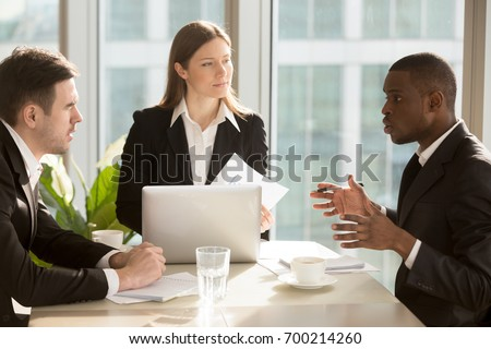 Multi-ethnic business team discussing project or idea sitting at office desk, partners working together, analyzing financial report, finding effective business solutions during corporate meeting