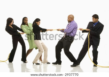 Multi-ethnic businessmen playing tug of war against businesswomen. - stock photo
