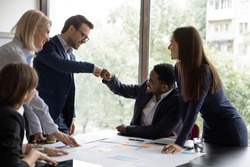 Multi ethnic businessmen project leaders fists bump celebrating corporate achievements, workmates meet in office boardroom surrounded by happy workmates. Reach common decision, share advance concept