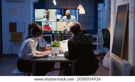 Multi ethnic businesspeople brainstorming company ideas during online videocall conference meeting discussing with remote teamwork. Diverse coworkers overworking in office room late at night Foto stock ©