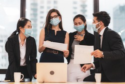 Multi ethnic businessperson (Caucasian, Asian) wear protective face mask discuss in office in CBD area. Concept of diversity people, new normal business office work after Covid 19 pandemic outbreak