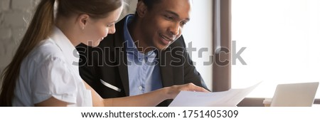 Multi ethnic colleagues analyzing report, financial advisor consult client people discuss agreement terms during meeting in office. Team work concept. Horizontal photo banner for website header design