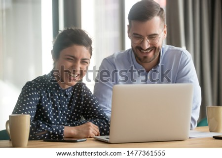 Multi-ethnic colleagues sit at desk working on project together use computer, telling jokes, laugh and humor brighten mood, key in creative thinking, increase effective workplace communication concept