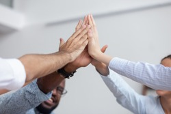Multi ethnic corporate office business team winners join hands give high five together, success gesture, startup triumph, professional victory, teamwork accomplishment teambuilding concept, close up