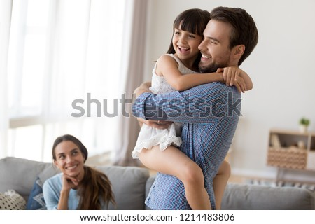 Multi-ethnic couple and kid in living room at home. Laughing young father hold on hands embrace little smiling daughter, mother sitting on couch looking at beloved people. Happy diverse family concept