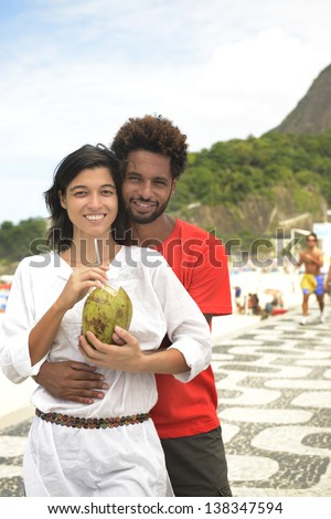 Multi ethnic couple of boyfriends friends tourists drinking coconut water on the edge of Rio de Janeiro.