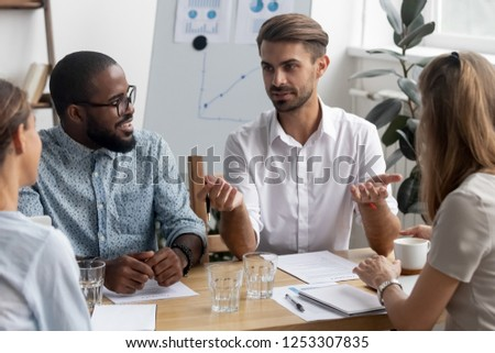 Multi-ethnic diverse friendly coworkers listens confident colleague sitting together in modern office conference room discuss new projects share business ideas and thoughts for reaching great results