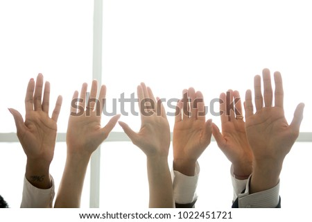 Multi-ethnic diverse people hands lifted up in the air, black and white palms raised as volunteering, initiative and engagement concept, business team training, activists get involved, close up view