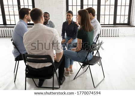 Multi ethnic employees discuss common project, taking part in team building activity meeting. Psychologist counsellor therapist speak at group therapy session, psychotherapy support and rehab concept