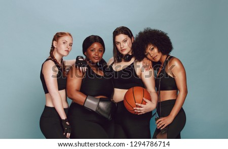 Multi-ethnic females in sportswear standing together with basketball, boxing gloves and skipping rope. Diverse group of women with sports equipment looking at camera against grey background.