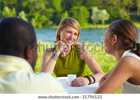 multi ethnic group having picnic outdoors and smiling