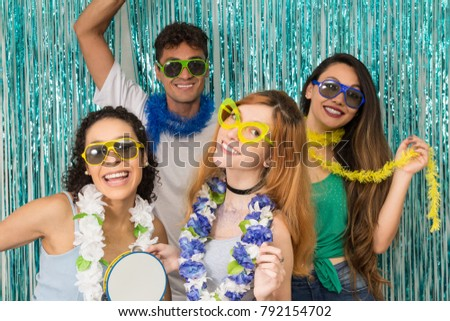 Multi ethnic group of Brazilian friends. Costumed revelers are happy and celebrating the Carnival with much celebration. People are wearing sunglasses and posing for the photo.
