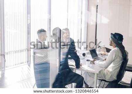 Multi-ethnic group of business partners of various ages and ethnicities gathered for meeting to discuss details of company expansion to the east - viewed through transparent glass wall.