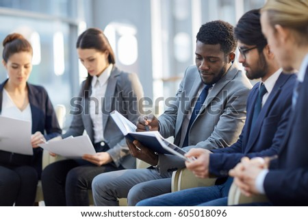Multi-ethnic group of  business people sitting in row in modern glass hall, focus on African-American businessman reading handout materials and making notes in book