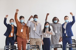 Multi-ethnic group of business people wearing masks and cheering while standing in row against white in conference room