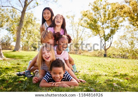 Multi-ethnic group of children lying in a pile in a park Foto stock ©