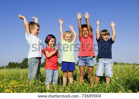 Multi-Ethnic group of children outdoors, arms raised