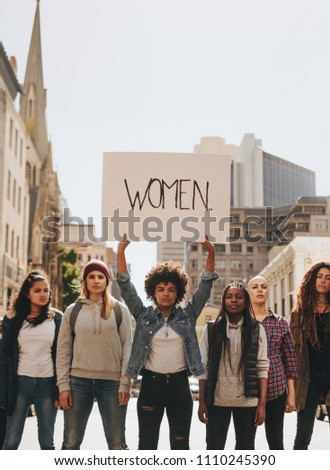 Multi-ethnic group of females protesting for women empowerment outdoors on road. Young african female with group holding banner sign during a protest.