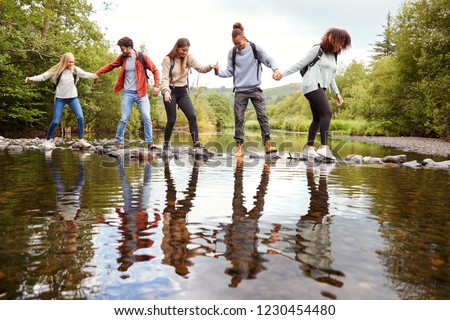 Multi ethnic group of five adult friends hold hands and help each other while carefully crossing a stream standing on stones during a hike