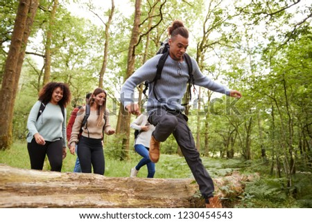 Multi ethnic group of five young adult friends running in a forest and jumping over fallen tree during a hike