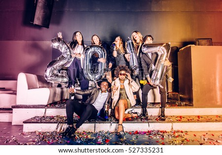 Multi-ethnic group of friends celebrating the end of the year in a nightclub - Sylvester party, clubbers having party on new year\'s eve