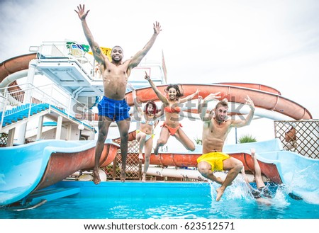 Multi-ethnic group of friends in a swimming pool - Young happy people having fun and enjoying summertime in a aquapark #623512571