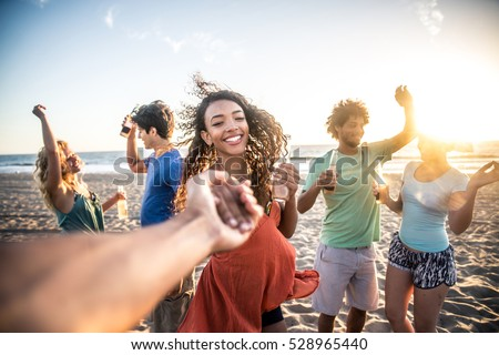 Shutterstock Multi-ethnic group of friends partying on the beach at sunset, pov prospective - Woman taking his boyfriend to dance
