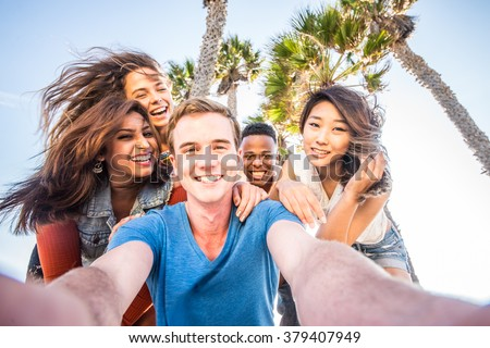 Multi-ethnic group of friends taking a self portrait picture with a camera phone - Cheerful people of diverse ethnics having fun and partying outdoors on a summer vacation