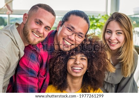Multi ethnic group of friends taking selfie indoor with a curly woman in foreground.two young women and two men in summer.people taking self portrait.Happy concept of students having fun together Stock photo ©