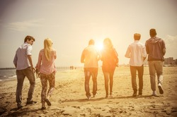 Multi-ethnic group of friends walking on the beach and talking - Group of young adults silhouettes at sunset