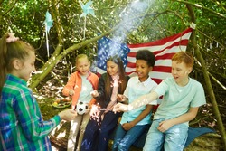 Multi-ethnic group of kids lighting sparklers while hiding under branches of big tree in forest or playing in back yard, copy space