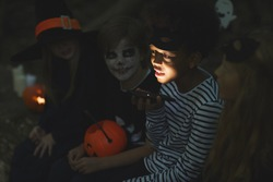 Multi-ethnic group of kids telling scary stories on Halloween, focus on African-American boy holding flashlight in foreground