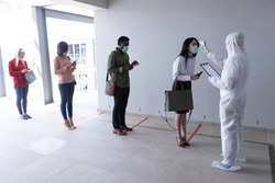 Multi ethnic group of male and female coworkers wearing face masks have temperature checked before entering office. Hygiene and social distancing in workplace during Coronavirus Covid 19 pandemic.