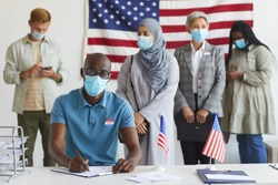 Multi-ethnic group of people standing in row and wearing masks at polling station on election day, focus on African-American man registering for voting
