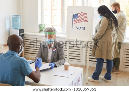 Multi-ethnic group of people wearing masks and PPE voting at polling station on post-pandemic election day, copy space Stock photo ©