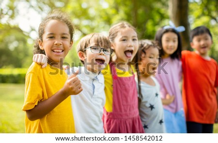 Multi-ethnic group of school children laughing and embracing #1458542012