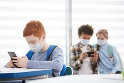 Multi-ethnic group of school children wearing face masks during epidemic, focus on red-haired teenage boy using smartphone in foreground, copy space