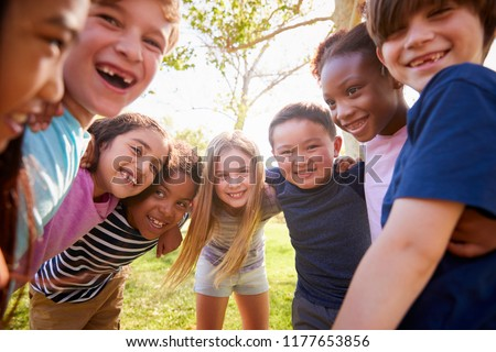 Multi-ethnic group of schoolchildren laughing and embracing