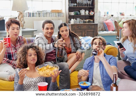 Multi ethnic group of  student friends bonding over sports match on TV drinking beer eating snacks  hanging out at home