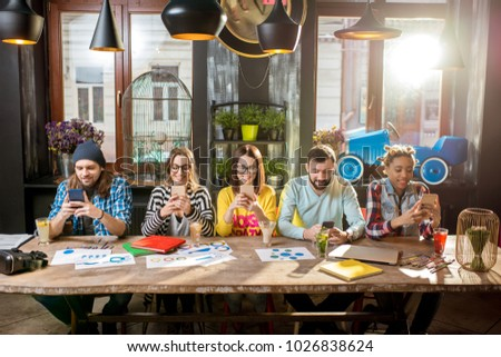 Multi ethnic group of young friends sitting with phones at the big table in the modern cafe interior Foto stock ©