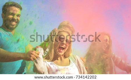 Multi-Ethnic Group of Young People Throw Colorful Powder in Celebration of Holi Festival. They Have Enormous Fun on this Clear Day by the Sea. Active emotions. #734142202