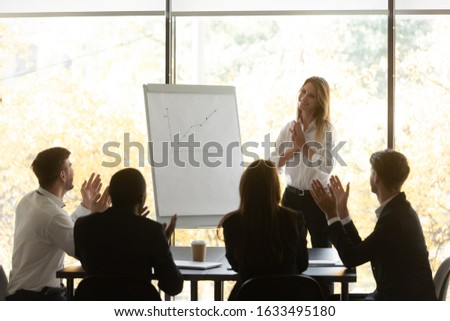 Multi-ethnic happy employees applaud expressing appreciation to woman speaker for successful flip chart presentation or educational seminar, female coach feels very touched by gratitude and attention