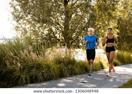 Multi-ethnic joggers exercising together outside in park #1306048948