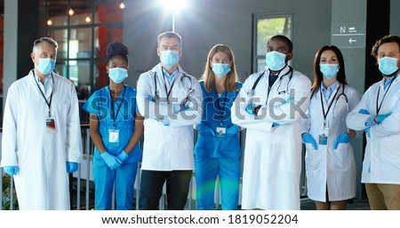 Multi ethnic male and female doctors. International medics in medical masks. Protected workers. Mixed-races physicians and nurses looking at camera. Clinic team. Docs at work in hospital.