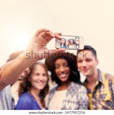 Multi-ethnic millenial friends taking a selfie photo with mobile phone on rooftop patio at sunset