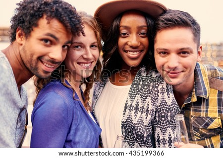 Multi-ethnic millenial group of friends taking a selfie photo with mobile phone on rooftop terrasse at sunset